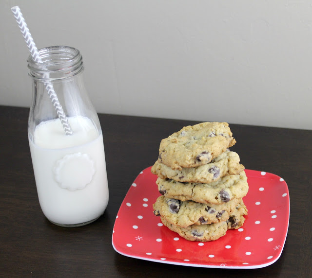 stacked chocolate chip cookies on a plate next to a glass of milk