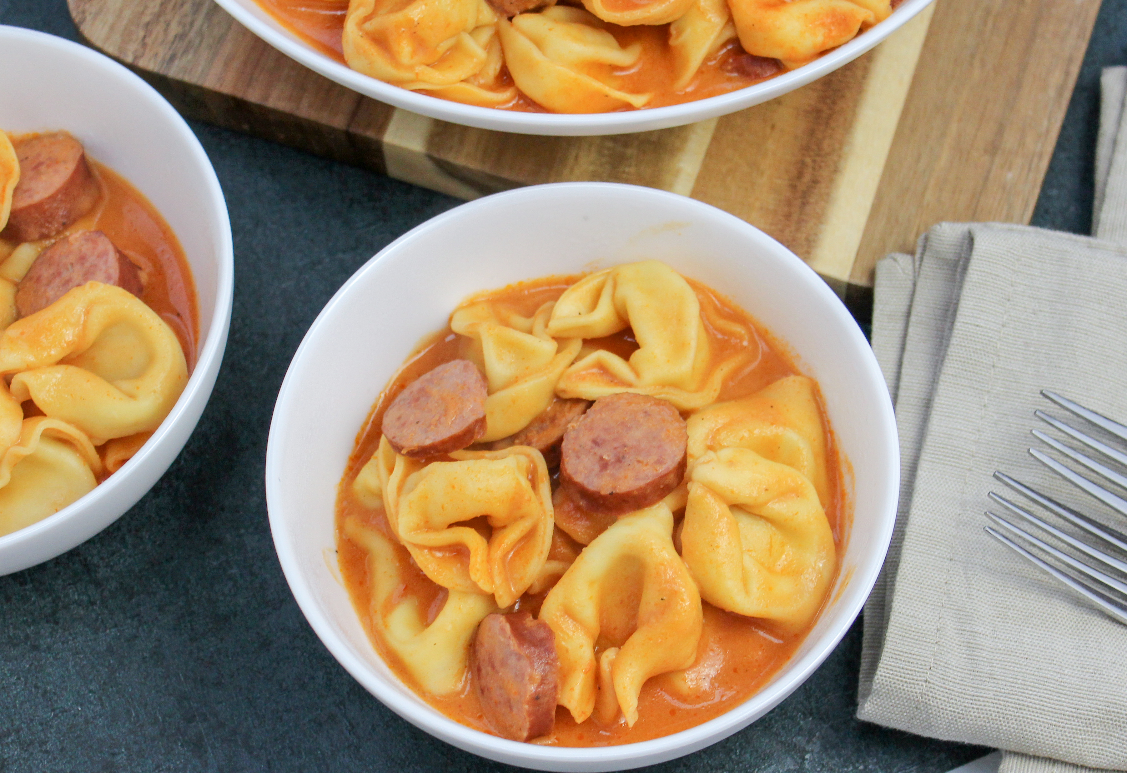 Tortellini and sliced smoked sausage in a whie bowl covered in tomato sauce