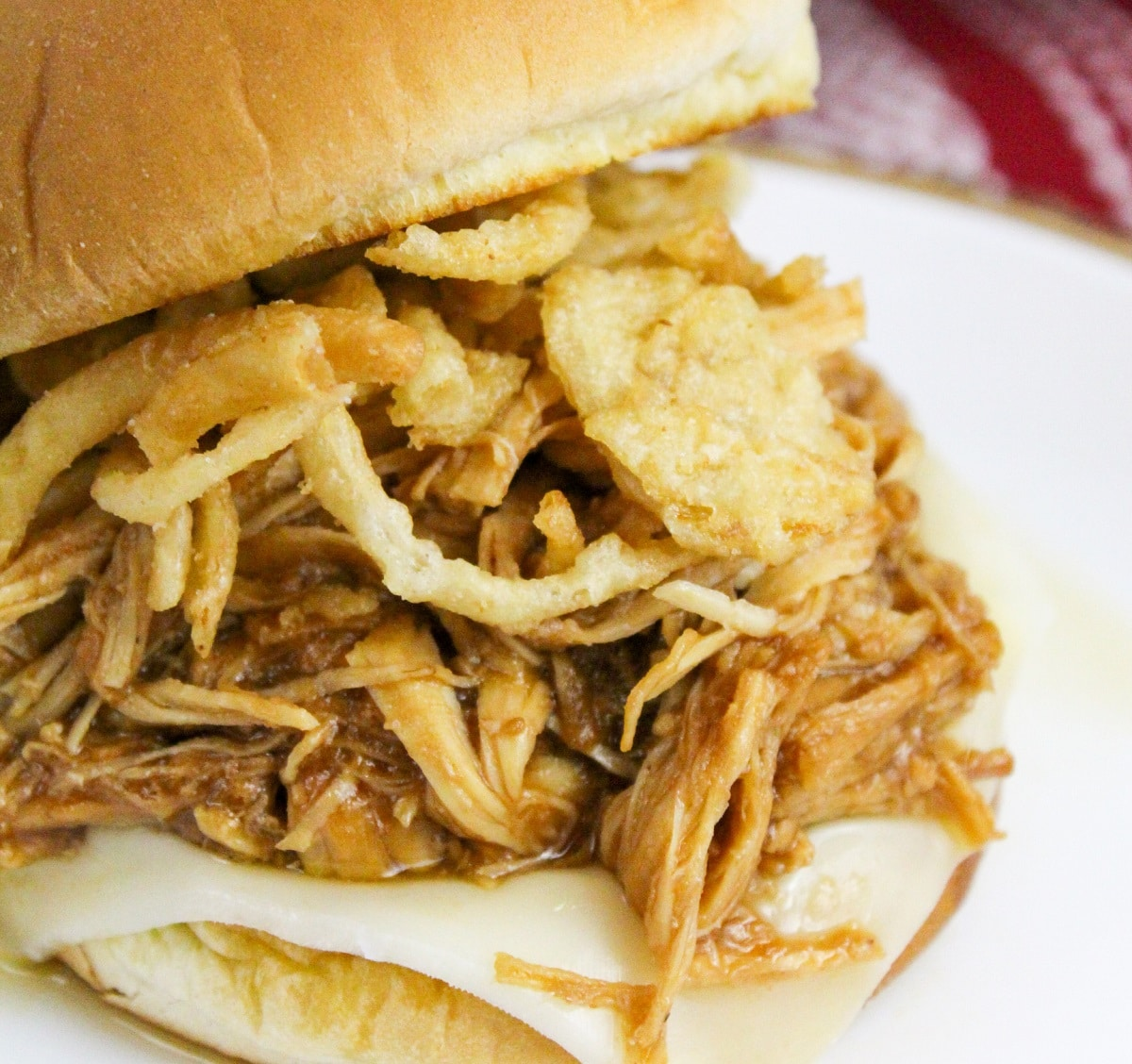 bbq cranberry chicken on a bun with cheese and onions