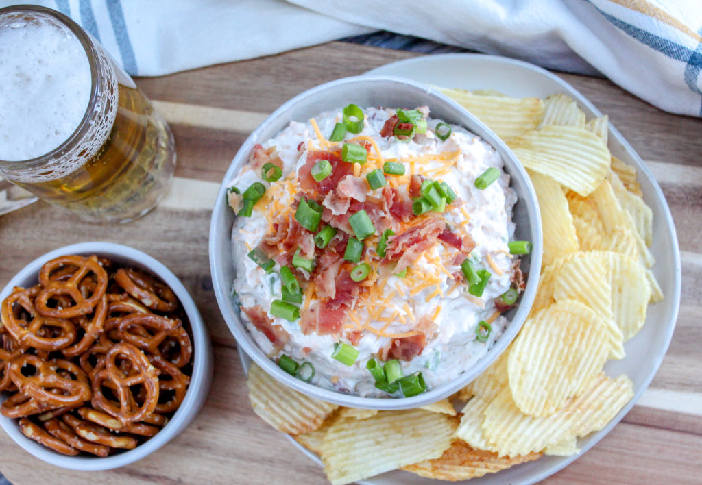beer dip in a bowl with chips and pretzels