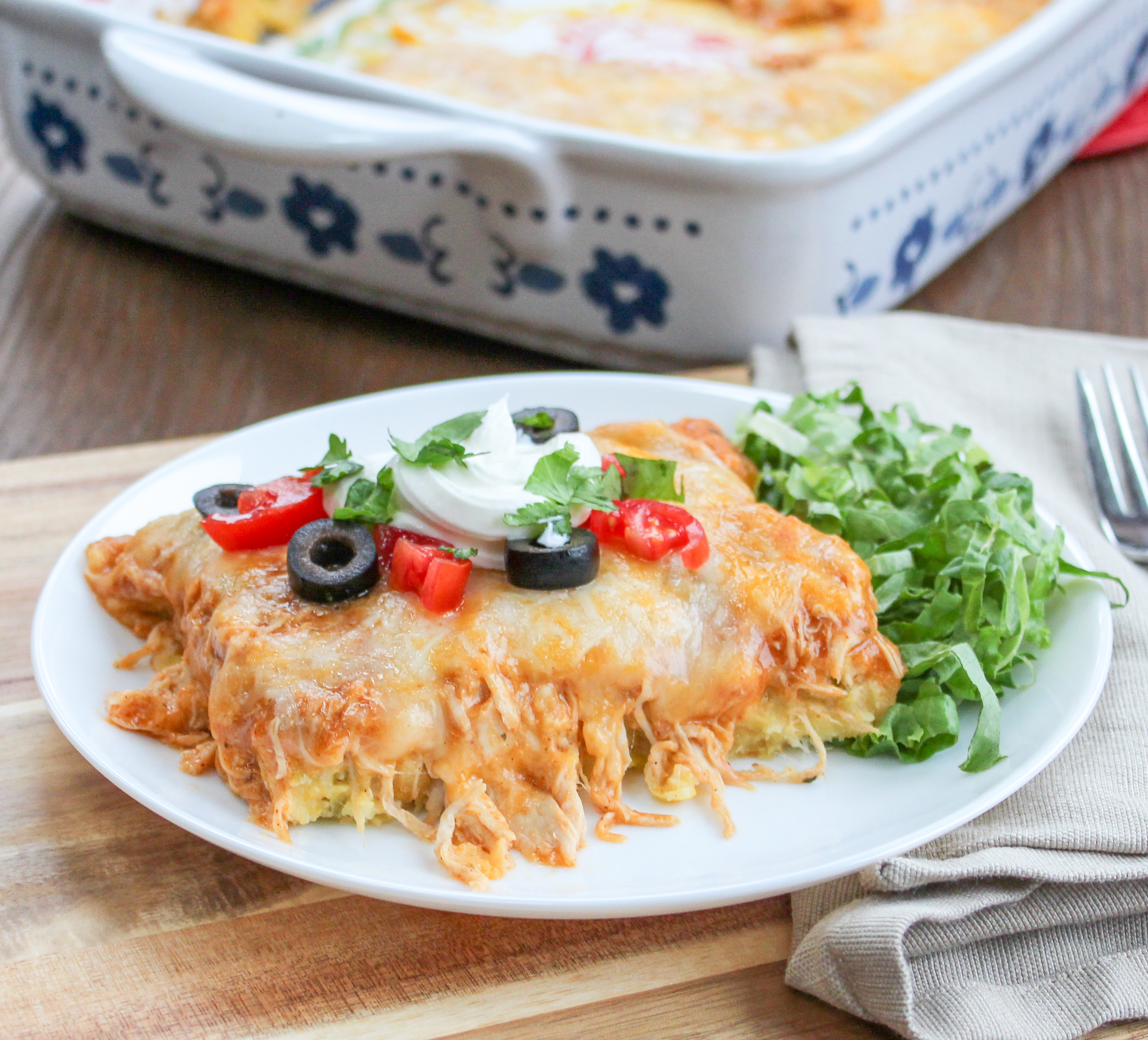 Portion of chicken tamale casserole with cheese on a plate with a side salad