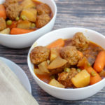 White bowl filled with meatballs, carrots, celery, potatoes and peas