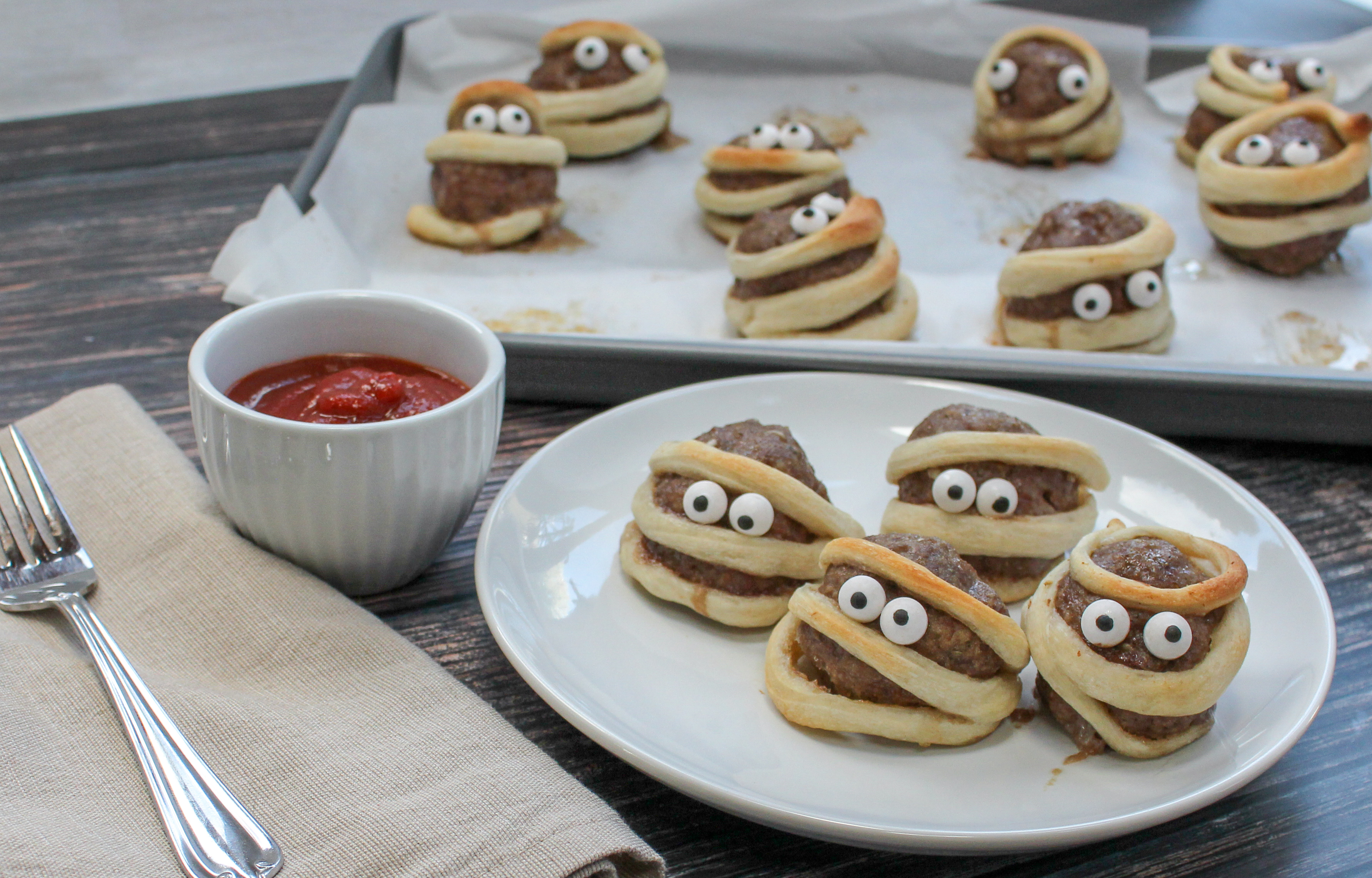 Meatballs wrapped in a strip of dough with candy eyes