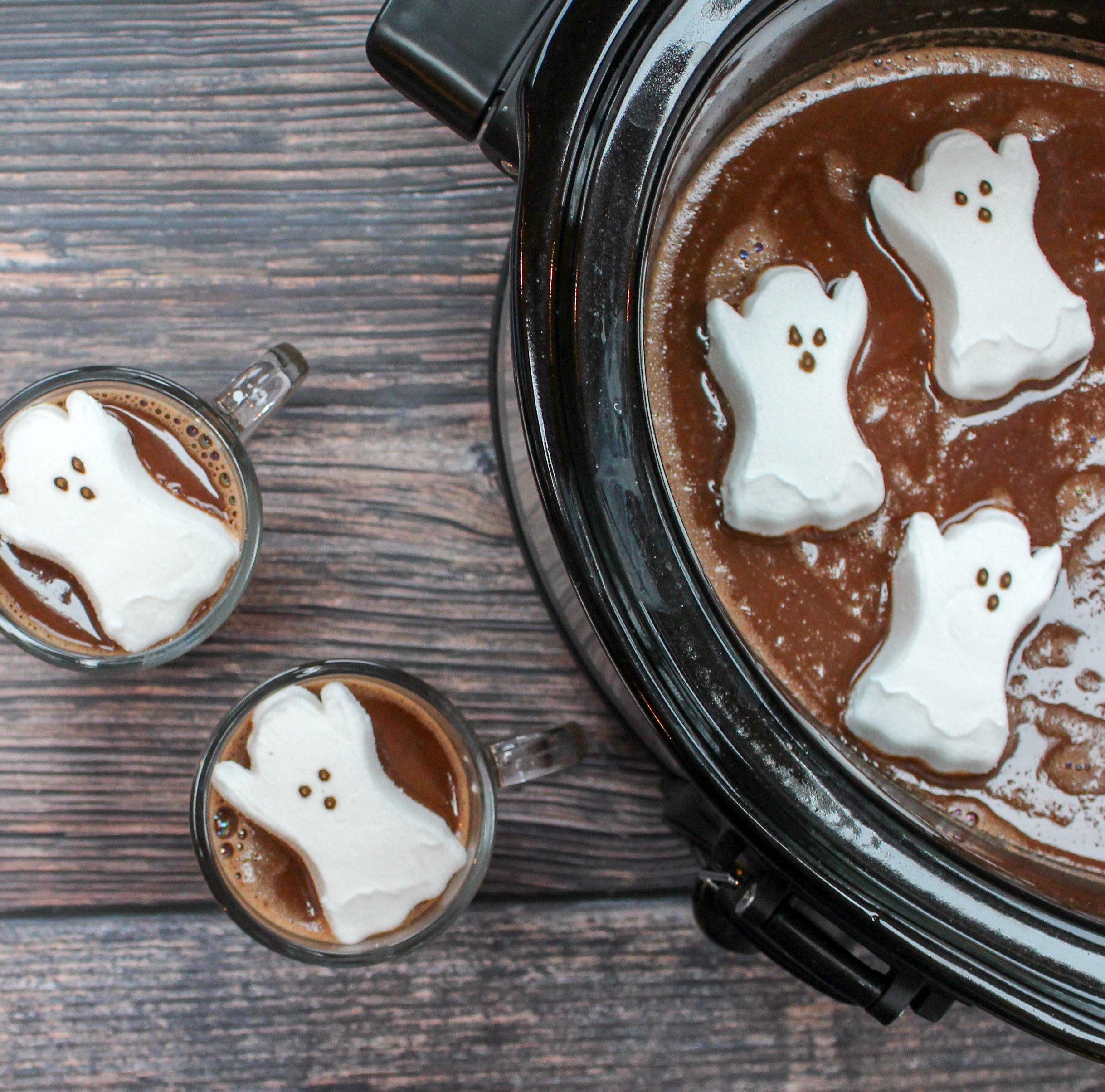 glasses filled with hot chocolate and topped with a ghost shaped marshmallow