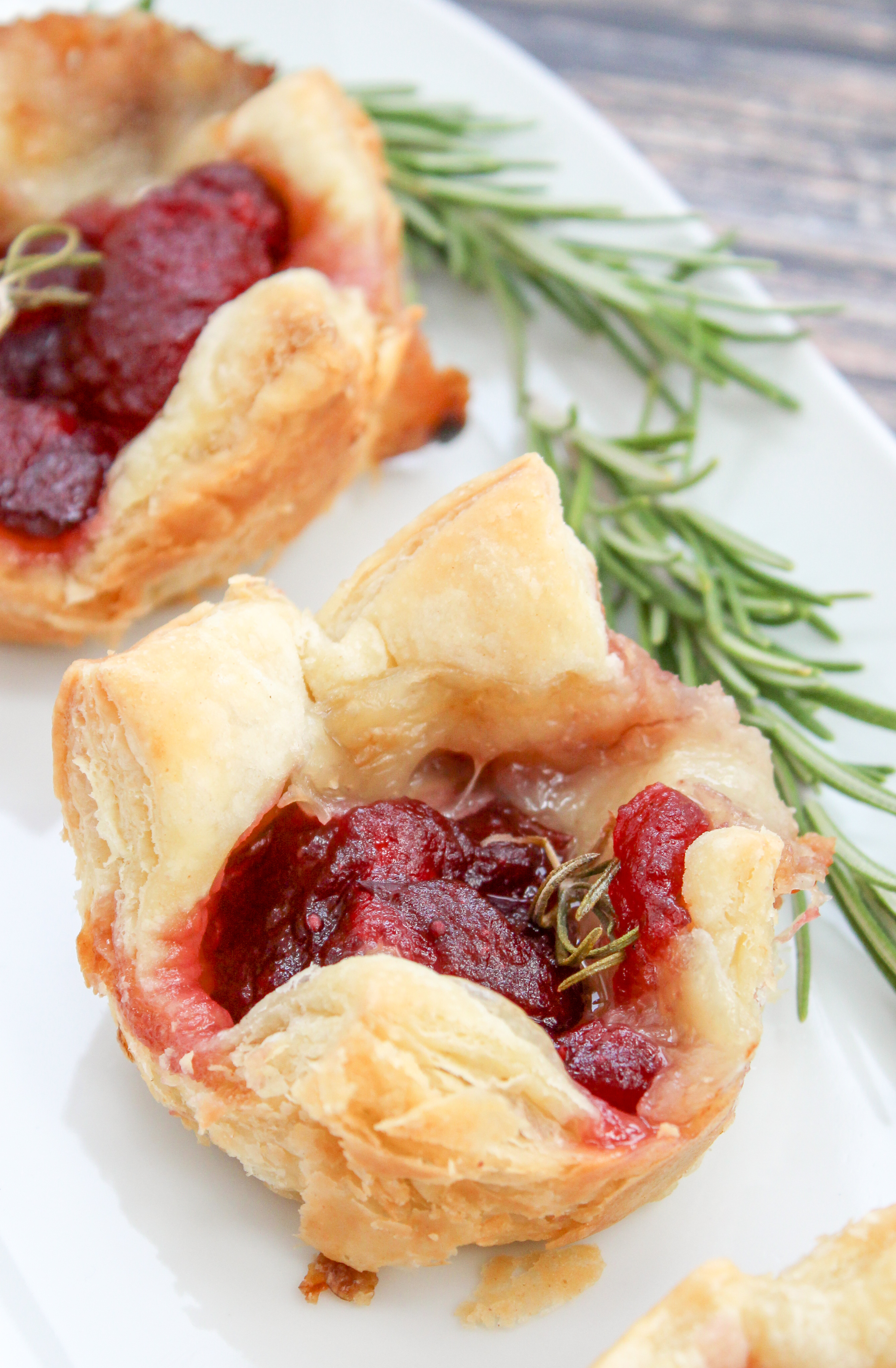 Cranberry and brie cheese in baked puffed pastry topped with rosemary
