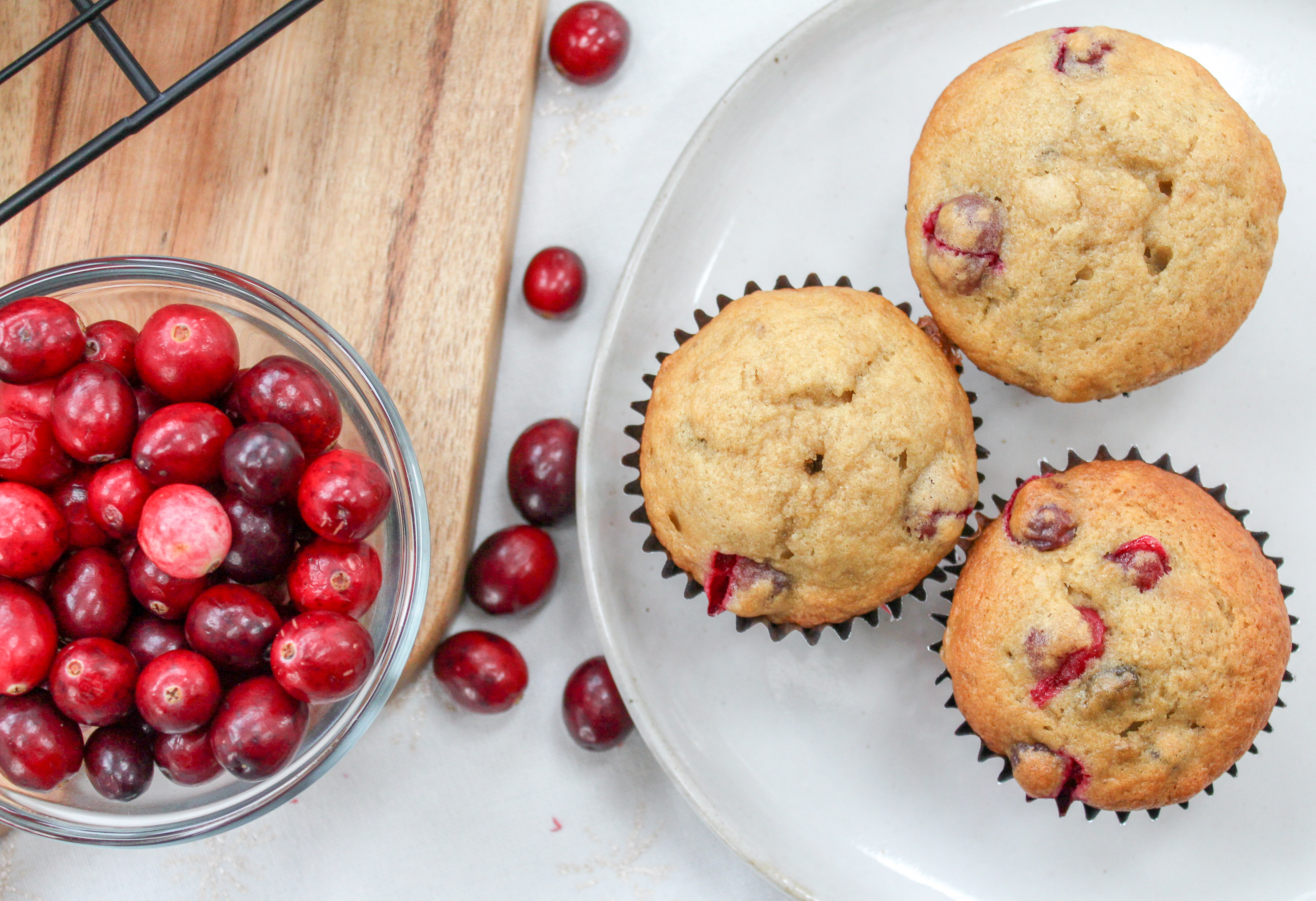 Several Muffins on a plate with cranberries on the side