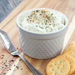 Spread in a white container wth crackers and a spreading knife
