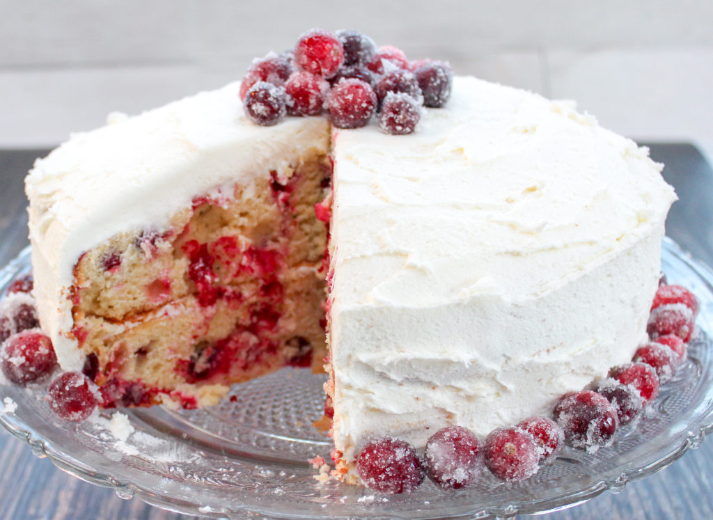 Cake topped with cranberries on a platter