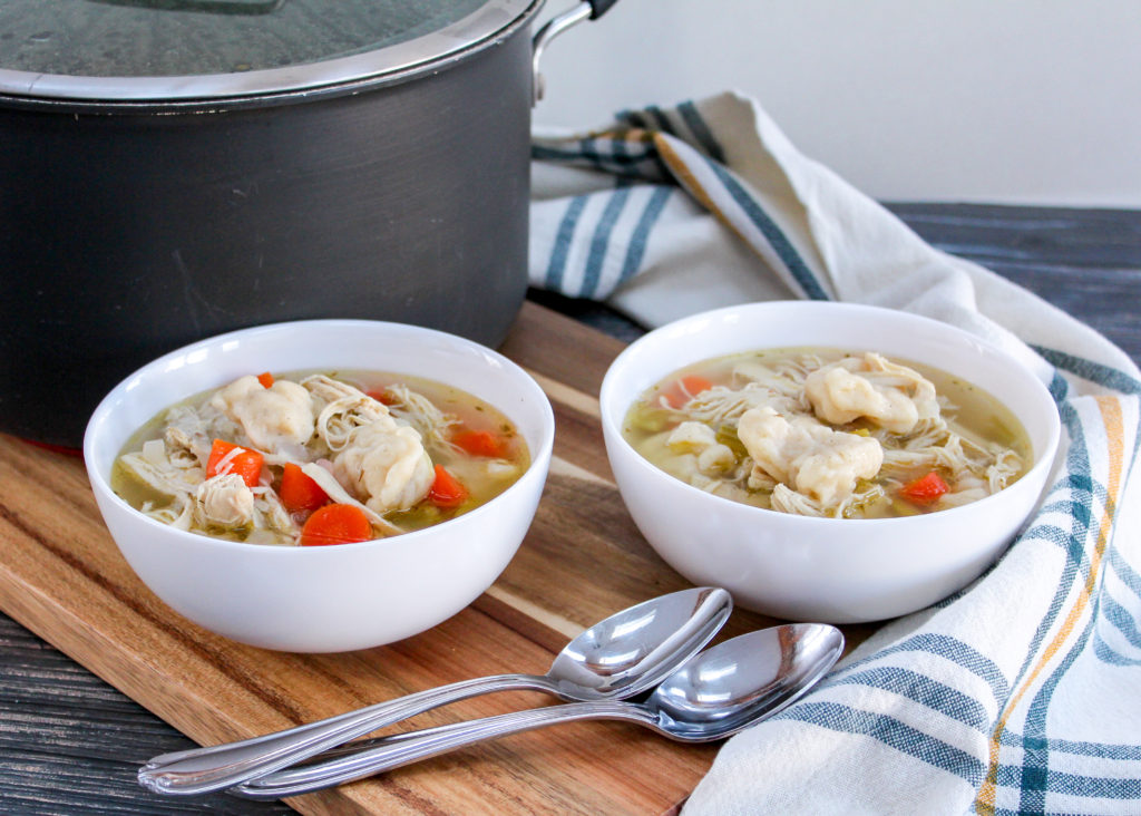 chicken dumpling soup in white bowls