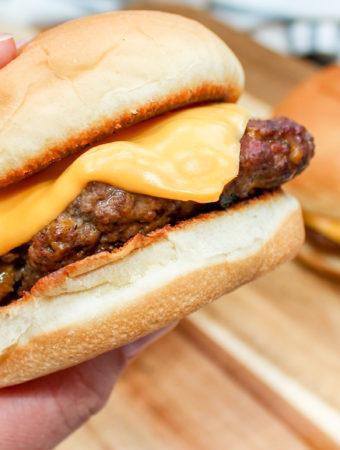 Cheeseburgers held in hand