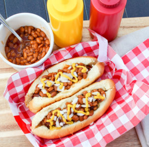 hot dog on the bun with beans and onion