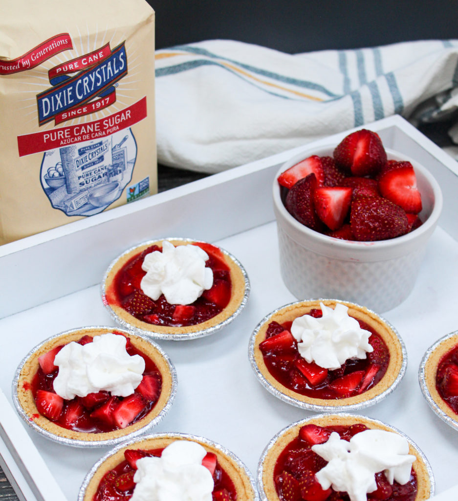 mini strawberry pies on a platter with whipped cream