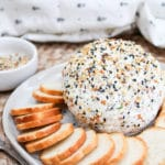 cheese ball on a plate with bagel chips around it