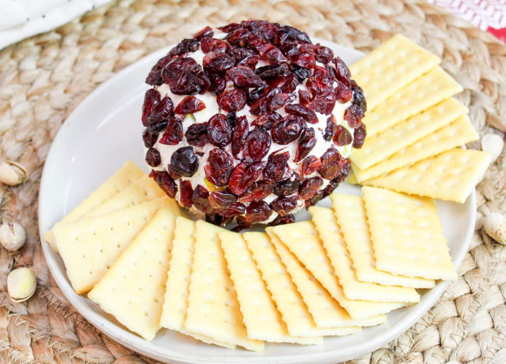 cheese ball on a plate with crackers around it