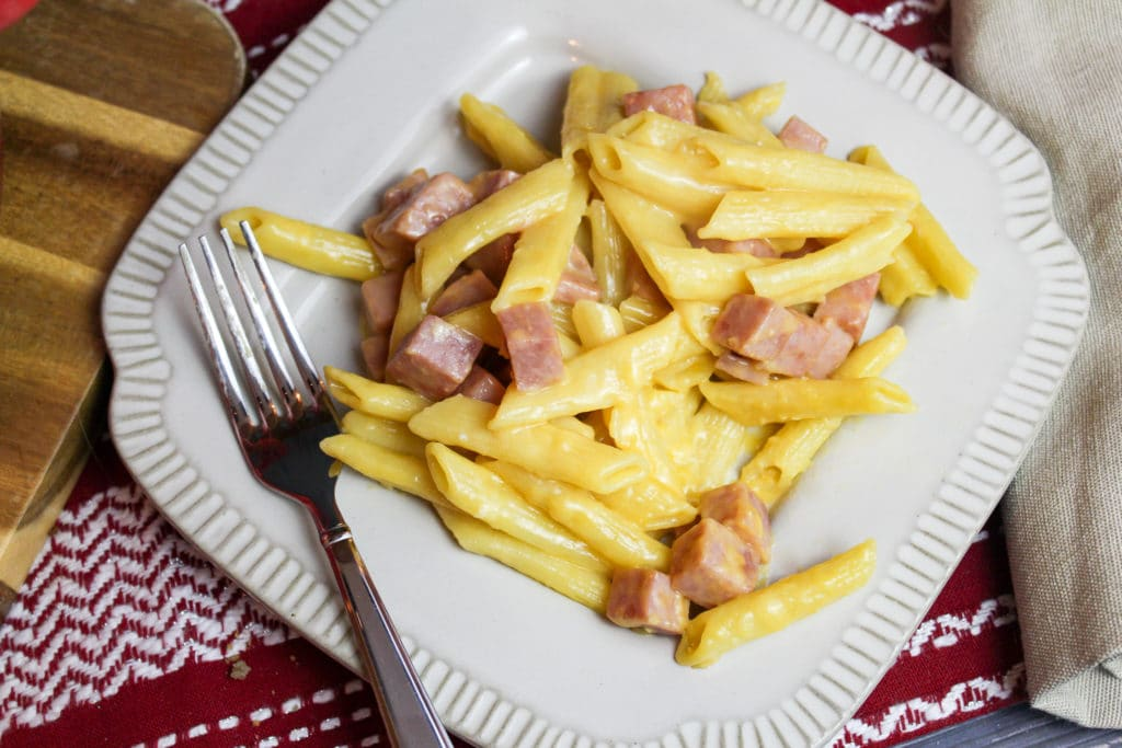 Ham and cheese pasta on a white dinner plate with a fork