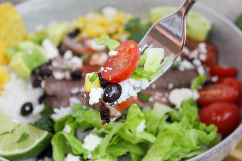 burrito bowl in white dish wit fork