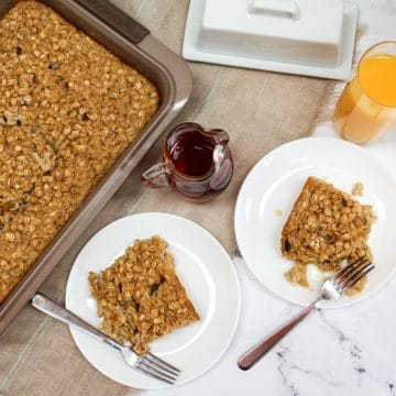 overhead photo of oatmeal in baking pan and two plated white dishes